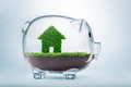 Saving to buy a house or home savings concept with grass growing in shape of inside transparent piggy bank Stock Photos