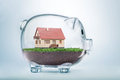 Saving to buy a house or home savings concept with model inside transparent piggy bank Royalty Free Stock Photo