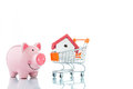 Saving to buy a house piggy bank and shopping trolley Stock Image