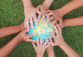 Saving the world multicultural hands touching earth globe Stock Images