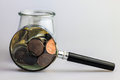 Savings concept with different coins in a glass jar and magnifier Stock Photography