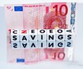 Savings held in euros text on small white cubes black uppercase letters with a ten euro note on a reflecting surface Stock Image