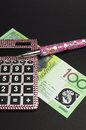 Savings and money management concept with calculator vertical australian hundred dollar note pink against a black background Stock Image
