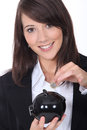 Savings in a moneybox brunette putting Royalty Free Stock Images