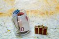 Savings for travel money in a jar over a touristic map small luggage on the side concept Stock Photo