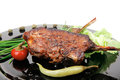 Savory plate grilled ribs over black with peppers and green salad Stock Photography