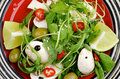 Savory salad spicy with arugula raw champignon mushrooms chili pepper lime sesame seeds and green olives closeup on red striped Stock Photo