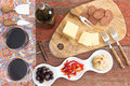 Savory snacks on a rustic table with red wine overhead view of two glasses and bottle of and havarti cheese spicy dried sausage Royalty Free Stock Photos