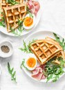 Savory waffles, boiled egg, ham and arugula on light background, top view. Appetizers, snack, brunch. Delicious healthy food conce