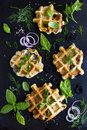 Savory waffles with cheese ham olives and herbs on black background top view Stock Photo