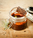 Savoury bbq basting sauce in a glass jar with a brush and sprig of fresh rosemary for seasoning and flavoring the meat Royalty Free Stock Photography