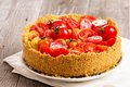 Savoury cheesecake with tomatoes on wooden table Royalty Free Stock Photo