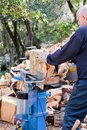 Saw cutting wood for winter. A man cutting firewood for the winter using a modern machine lumber saw. Royalty Free Stock Photo