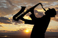 Saxophonist man playing on saxophone against the background of sunset Stock Photos