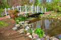Sayen park botanical garden ornamental foot bridge gardens on picturesque bucolic pond with flowering springtime trees and walking Stock Photo