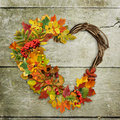 Scabrous wooden background with a wreath of autumn leaves and berries in heart shape Royalty Free Stock Photo