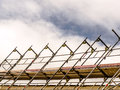 Scaffold parts of a raised with pipes and planks against the cloudy sky Stock Photography