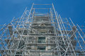 Scaffold surrounds this old pagoda in against a deep blue sky Stock Photo