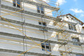 Scaffolding near a house under construction for external plaster works, high apartment building in city, white wall and window, ye Royalty Free Stock Photo