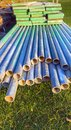Scaffolding poles and planks lying on grass Stock Photos