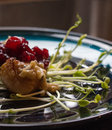 Scallop appetizer on bed of pea sprouts with cranberry compote Royalty Free Stock Photo