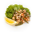 Scallop scallops with young pods of beans in sauce on a white background decorated dokoy lemon and lettuce Stock Photo