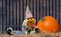 Scarecrow and pumpkin on hay Royalty Free Stock Photo