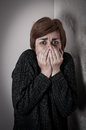 Scared and abused woman covering her mouth with her hands low key Stock Photography