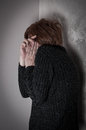 Scared and abused woman with hands on the head low key Stock Photography
