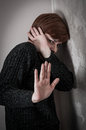 Scared and abused woman with one hand one the head the other arm stretched low key Stock Photography