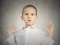 Scared child boy closeup portrait headshot hands up in air opened mouth looking at you camera isolated grey wall background human Stock Photos
