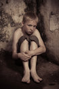 Scared child in corner of dungeon apprehensive single imprisoned male wearing shorts sitting on floor with arms around knees dark Stock Images