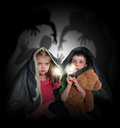 Scared children looking at night shadows two little are hiding under a blanket black scary monster ghosts in the background with Royalty Free Stock Images