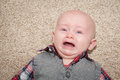 Scared crying baby with mouth and eyes open up close his gums and tongue are visible Stock Image