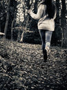 Scared girl running teenage away from camera in woods Royalty Free Stock Images