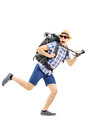Scared hiker with backpack and camera running away full length portrait of a isolated on white background Royalty Free Stock Photography