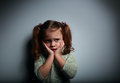 Scared kid girl with hands near face looking with horror on dark background empty space for text Royalty Free Stock Image