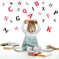 Scared little girl sitting surrounded by books and alphabetical Royalty Free Stock Photo