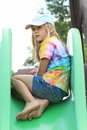 Scared little girl on a slide barefoot in colorful t shirt blue shorts and cap sitting green Royalty Free Stock Photos