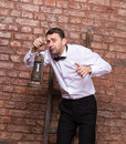 Scared man searching with an oil lamp holding it in front of him as he stands against a brick wall a terrified anxious Stock Photography