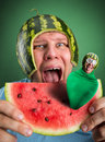 Scared man with watermelon helmet trying to eat slice parasitic caterpillar in it Royalty Free Stock Photography