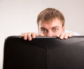 Scared man a young hiding behind a office chair Stock Photo