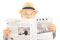 Scared senior man with glasses hiding behind a newspaper isolated on white background Stock Photos