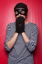 Scared thief wants your money standing at the red background Stock Photography