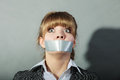Scared woman with mouth taped shut. Censorship. Royalty Free Stock Photo