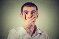 Scared young man with hand over his mouth, stunned and speechless Royalty Free Stock Photo