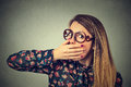 Scared young woman in glasses covering with hand her mouth