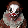 Scarier clown a with sharp pointy teeth glaring at you isolated on a black background Royalty Free Stock Images