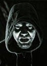 Scary evil man with hood in darkness Stock Images