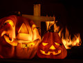 Scary halloween night aggresive burning fire on cemetery near cross terrible carved pumpkin face laughing holiday party horror Stock Photography